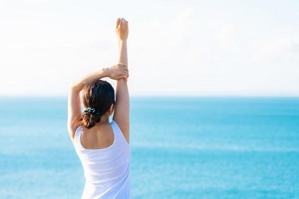海に向かって伸びをする女性